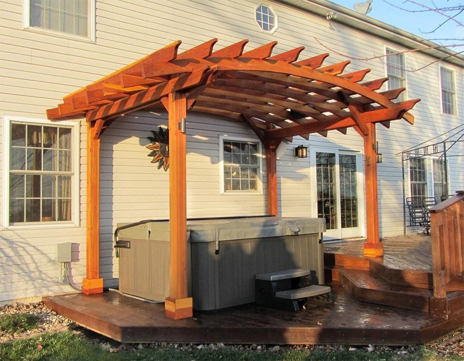 Hot tub pergola kit with an arched roof installed on a multi-tiered wood deck