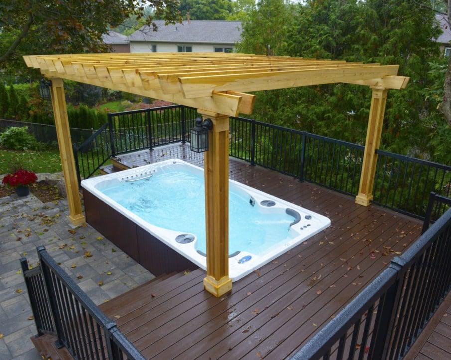 Simple hot tub under pergola installation on a wood deck