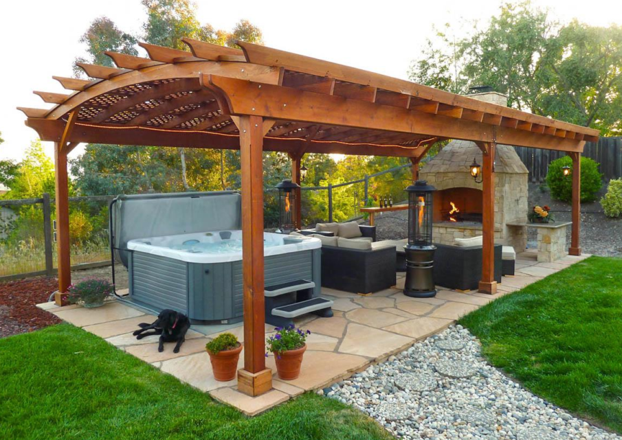 An oversized pergola that houses a hot tub, a fireplace and a seating area