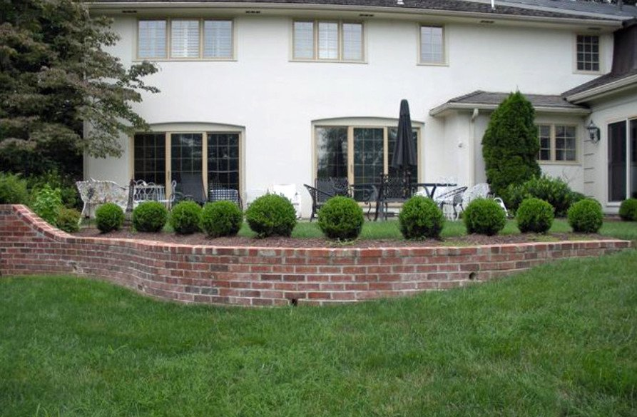 Brick retaining wall landscaped to provide privacy to patio