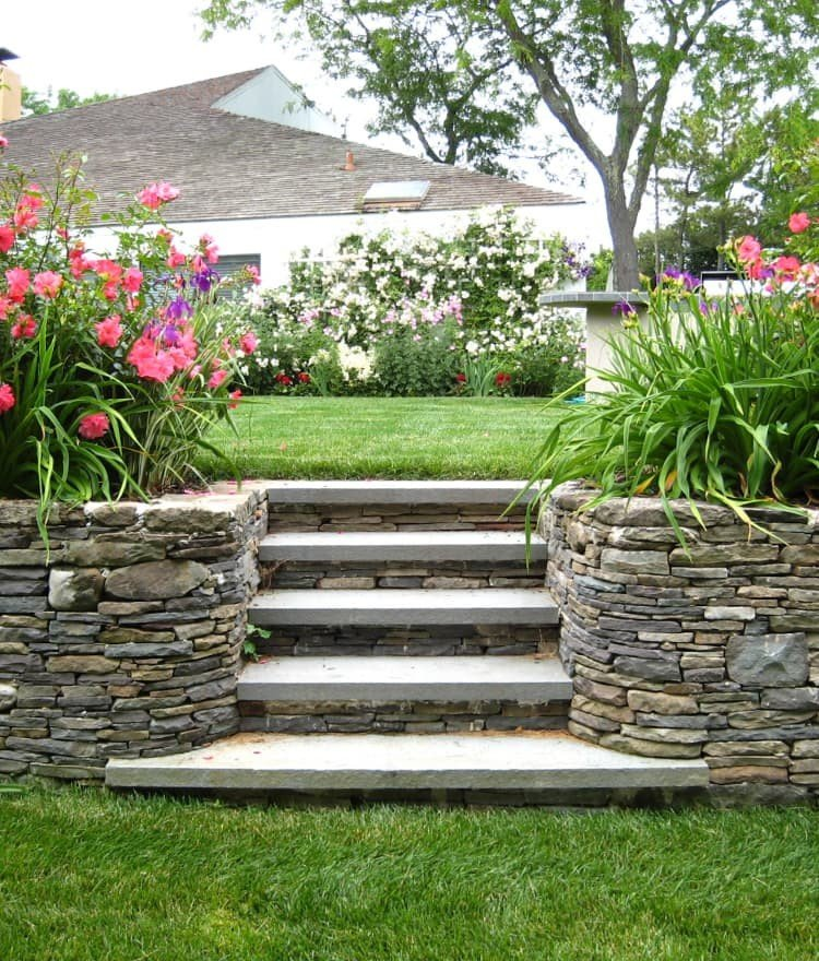 Fieldstone wall with steps - part of a landscaped backyard