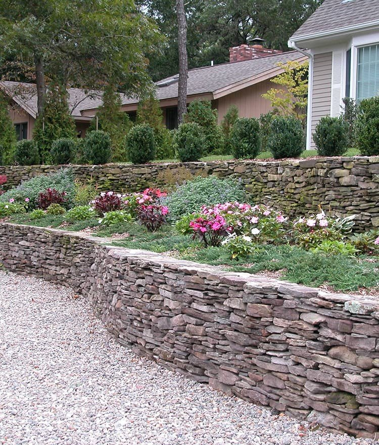 Two-tiered retaining wall constructed of natural fieldstone