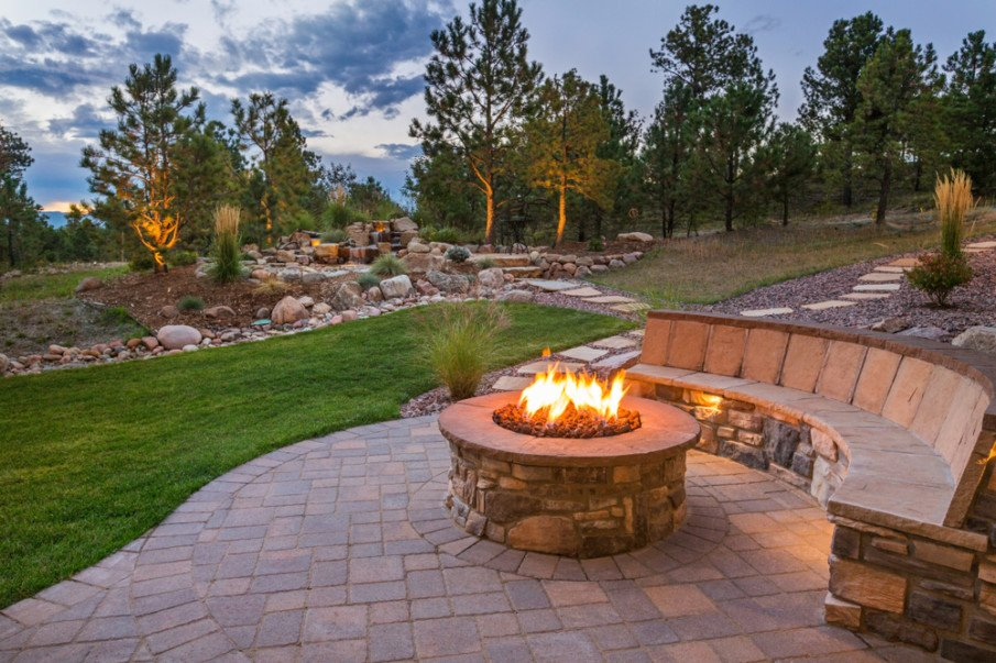 Cobblestone patio designed wtth firepit and bench