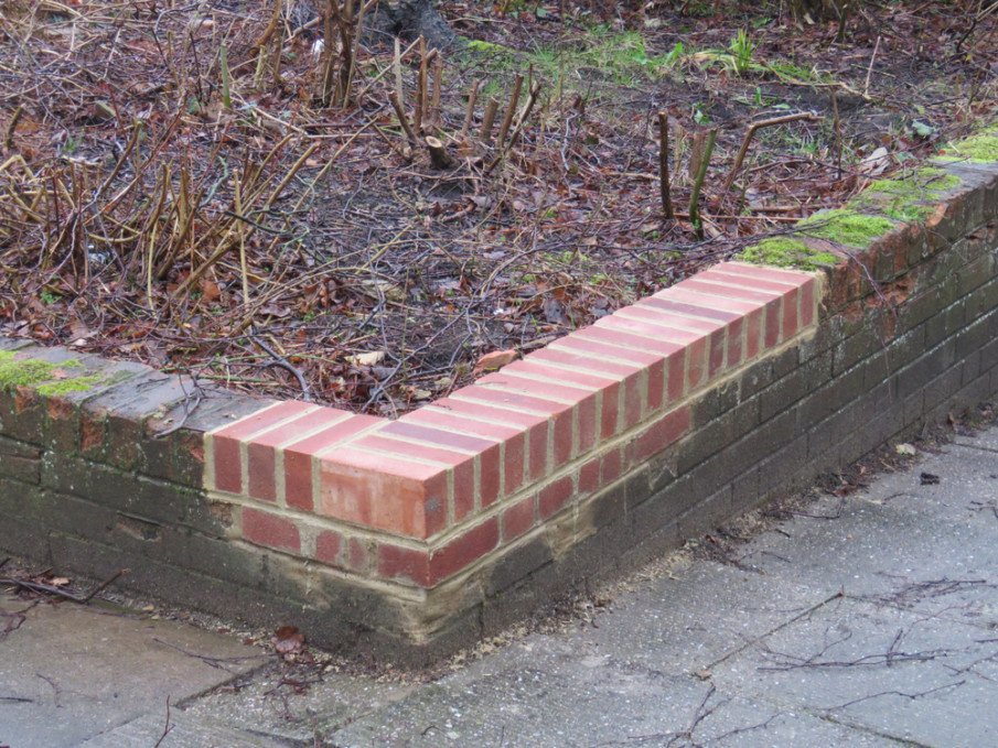 Corner of low retaining wall repaired with replacement bricks