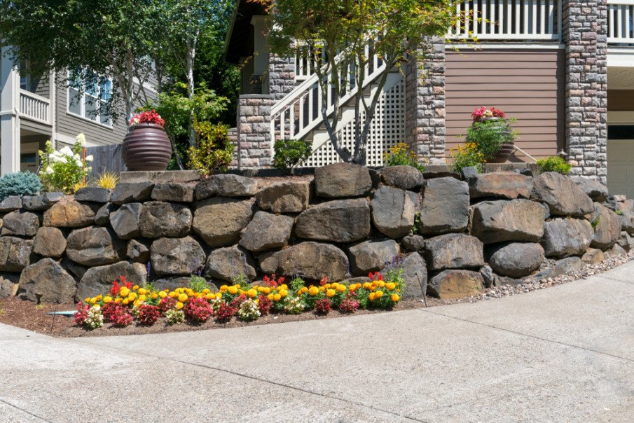 Front yard retaining wall made of large cut rocks