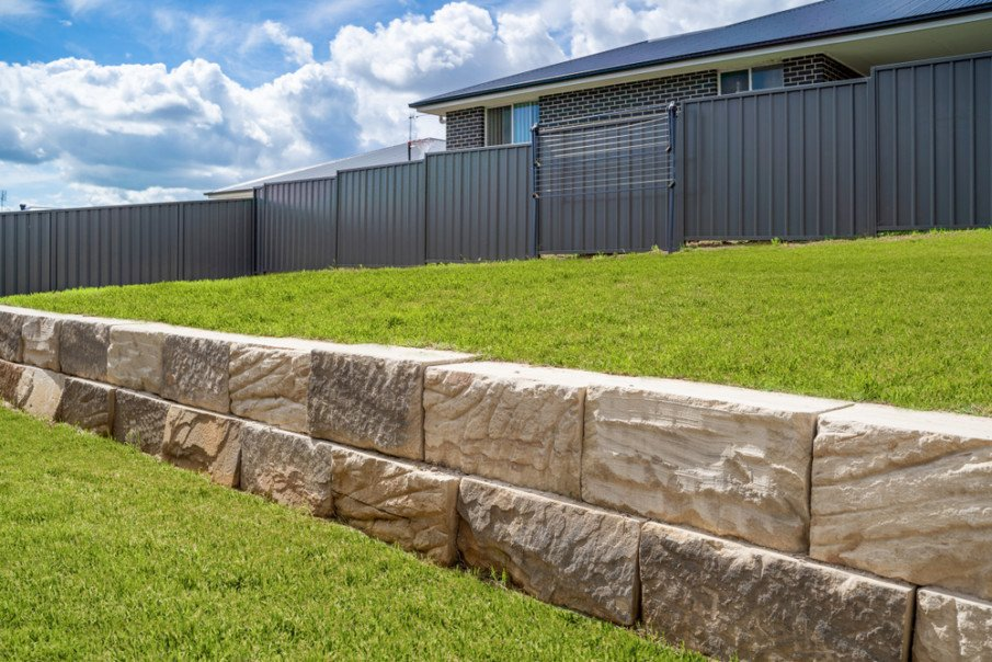 Sandstone retaining wall to stabilize grassy backyard