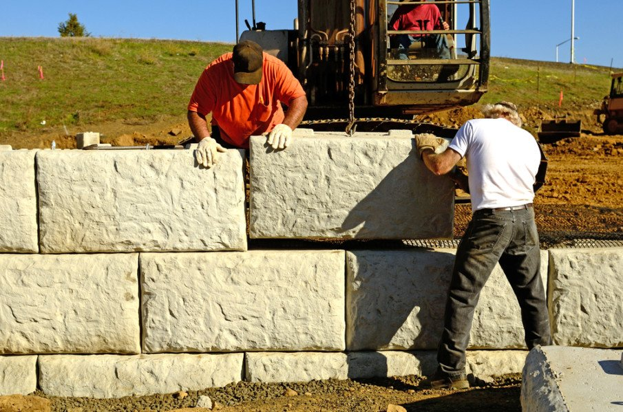 Tall retaining wall constructed of large cement blocks