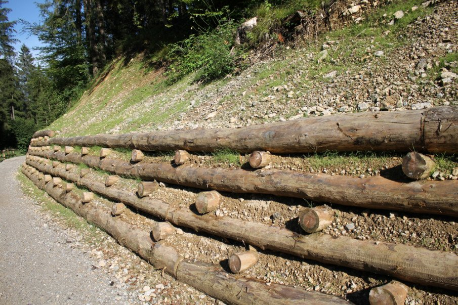 Log crib retaining wall keeps loose materials anchored in place