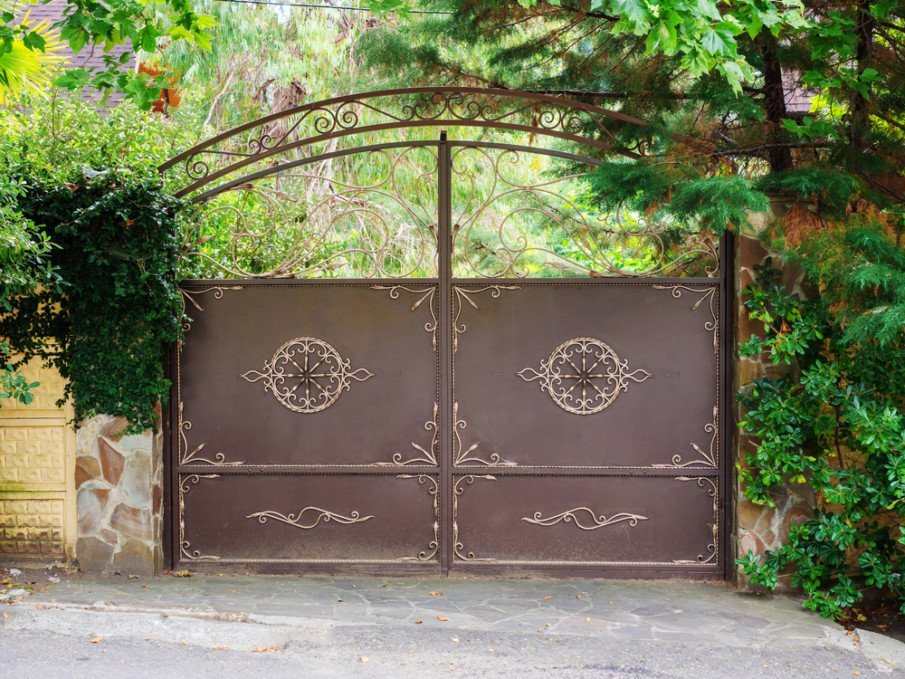 A brown wrought iron gate with golden details