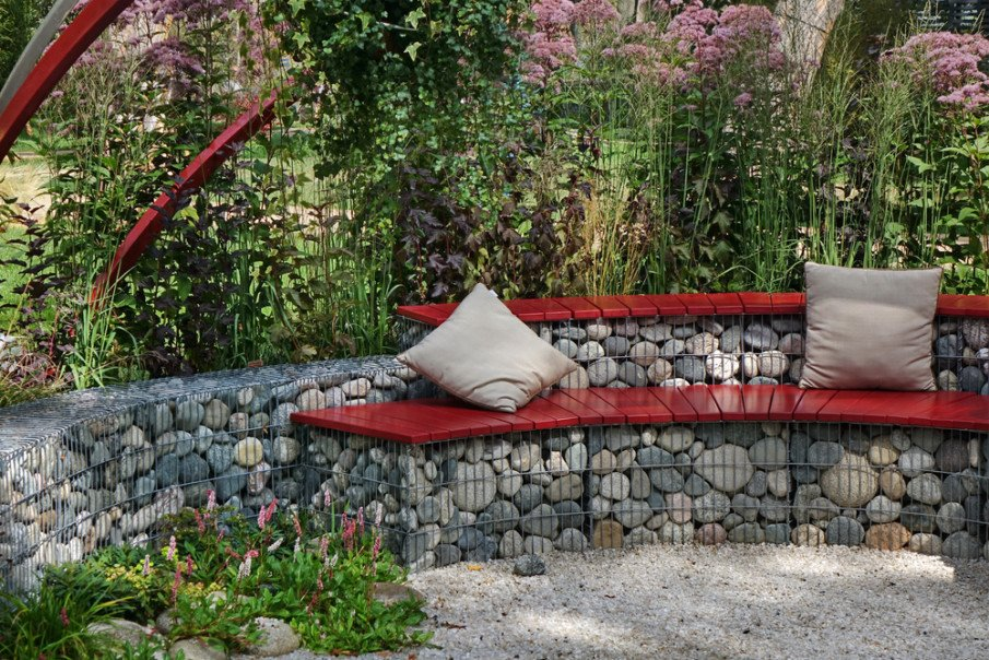 Two-tiered gabion wall of stone creates wood seating area
