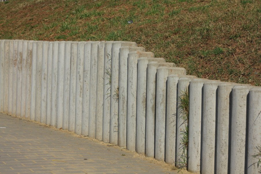 Tall retaining wall separates sidewalk from property