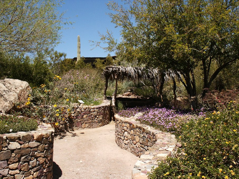 Curved boulder retaining walls with boulder capstones