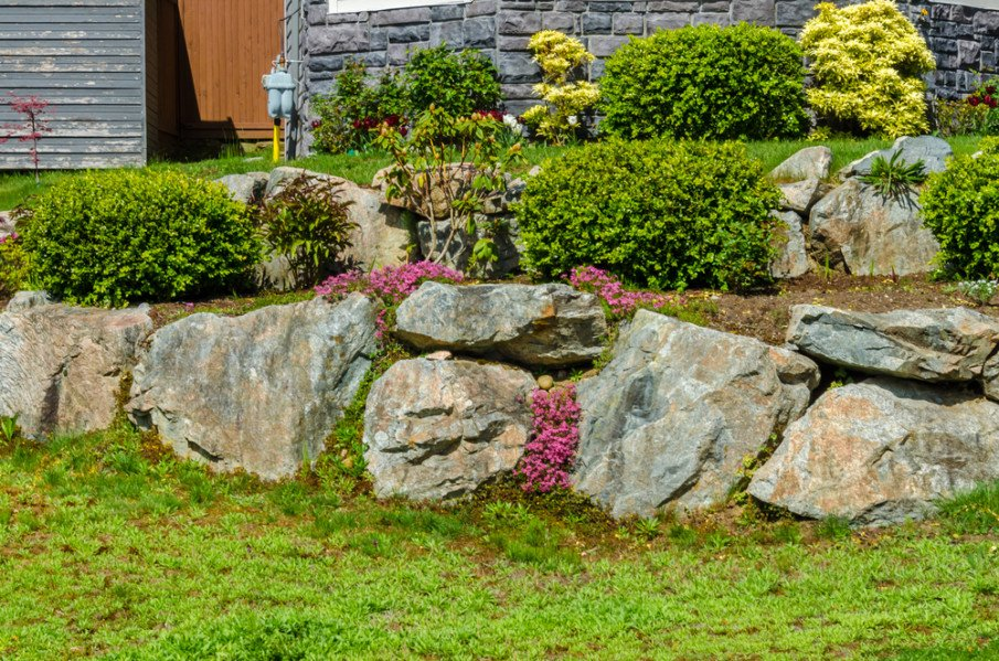 Tiered retaining wall landscape design with boulders
