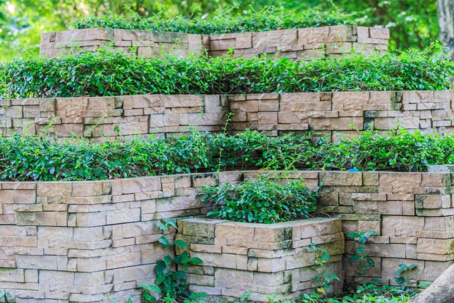 Corner natural stone retaining walls in landscaped garden