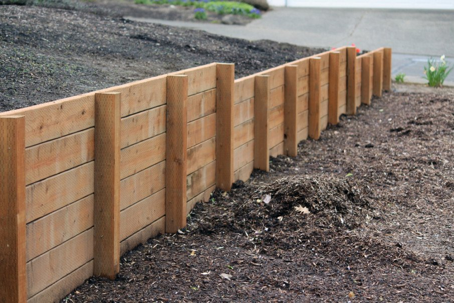 Use a pressurized wood retaining wall to divide two properties