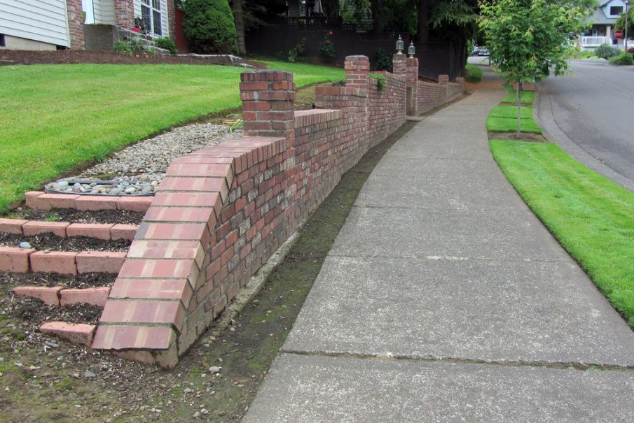 Brick retaining wall finished with caps made of one wide brick