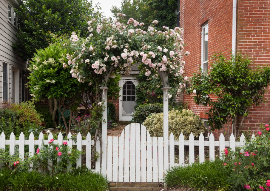 Front entry arbor with gate topped with colorful flowers, and a white picket fence