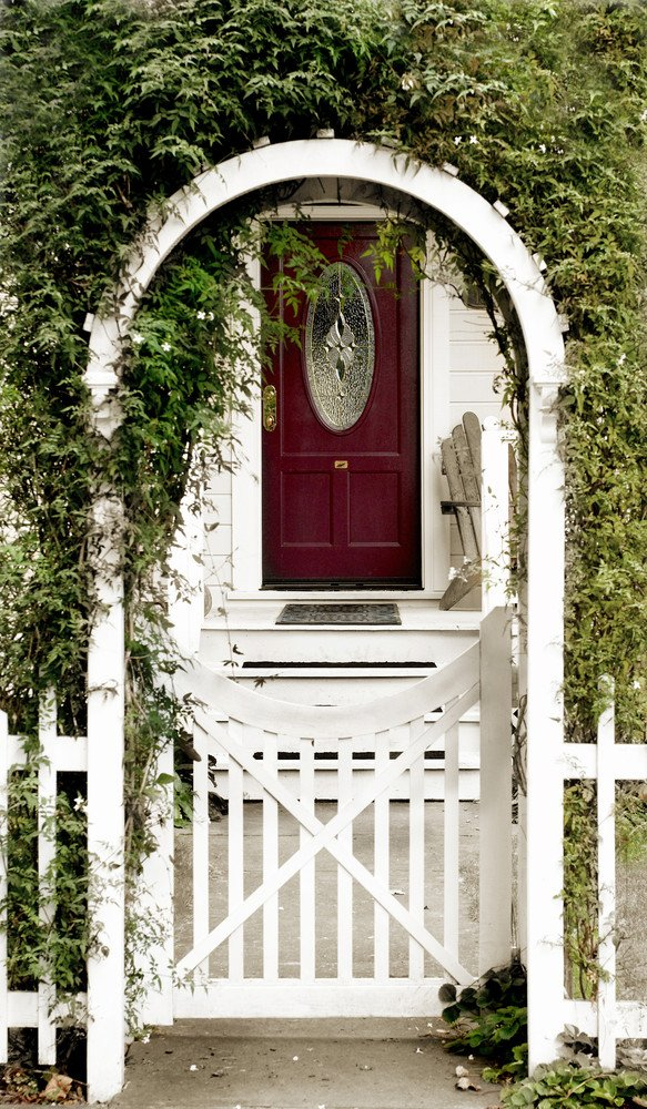 White vinyl arbor gate covered with greenery