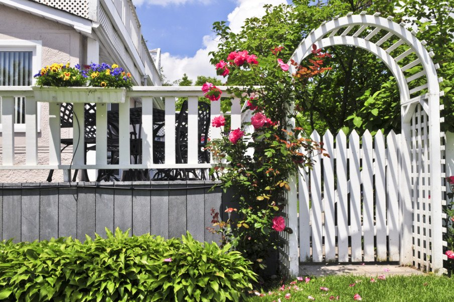 Arched house entry arbor with gate and matching white deck railing