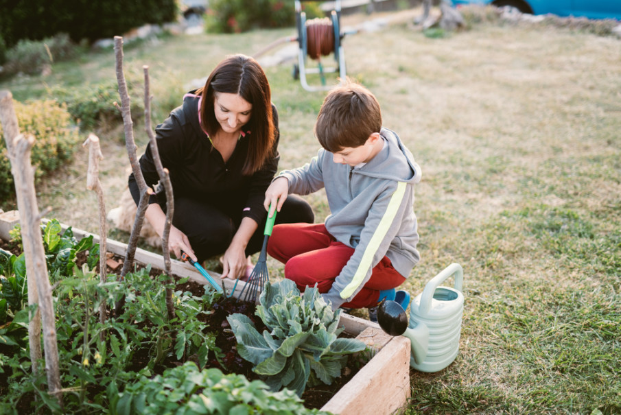 Mother and her child are gardening together